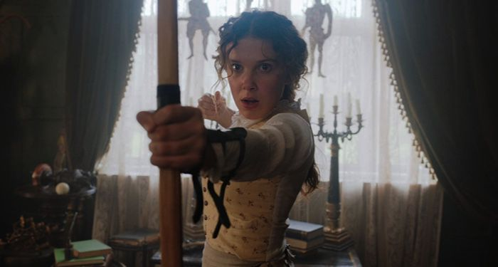 movie still from Netflix's ENOLA HOLMES picturing Enola holding a bow https://www.imdb.com/title/tt7846844/mediaviewer/rm1532338945