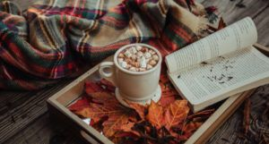 image of a plaid scarf and a tray filled with orange leaves, a mug of hot cocoa, and an open book https://unsplash.com/photos/JhxGkGgd3Sw