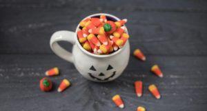 candy corn in a pumpkin mug