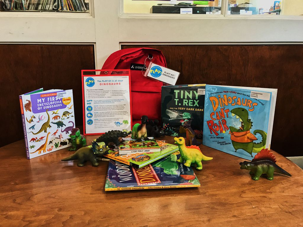 Books, dinosaur figurines, and a red backpack