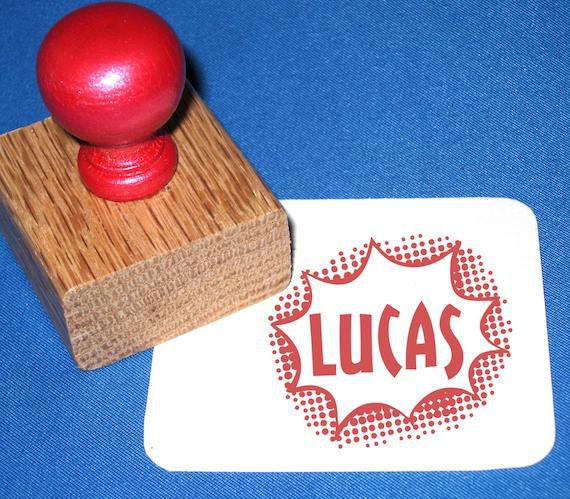 """Wooden stamp with red handle. On paper it says """"Lucas"""" in a speech bubble burst."""