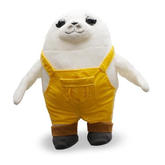 White seal with legs in yellow overalls and grey and brown boots.