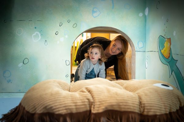 White woman and white girl poke their heads through a small opening into a room with bubbles and sea creatures on the walls