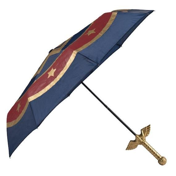 Open umbrella in red, blue and gold. The handle is a sword with wings.
