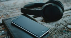 image of a pair of black headphones and a cell phone resting on a journal https://unsplash.com/photos/v0HbU2CNJFs