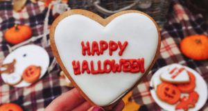 cookie with Happy Halloween in icing and Halloween and pumpkin cookies in background