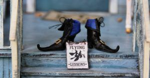"witch shoes with ""flying lessons"" sign on porch steps"