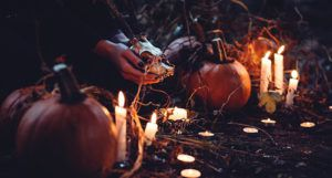 a photo of a pair of brown-skinned hands with black nail polish holding an animal skull; there are jackolanterns, lit candles, and bits of hay and leaves in the surrounding area