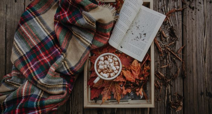 autumn or fall leaves with open book cocoa and blanket