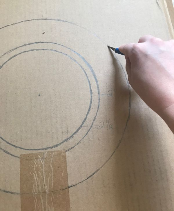 Picture of a hand holding a craft knife cutting out a cardboard circle