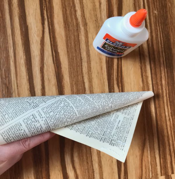 Picture of glue bottle with paper cone, one edge slightly unrolled, with glue on the corner