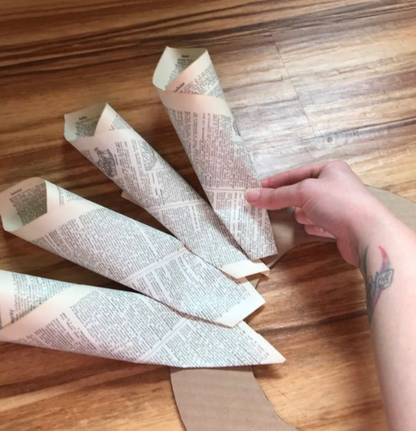 A picture of a hand placing a book page cone on a cardboard wreath
