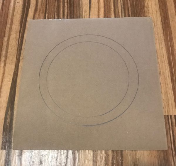 Picture of square piece of cardboard with two circles drawn in the middle