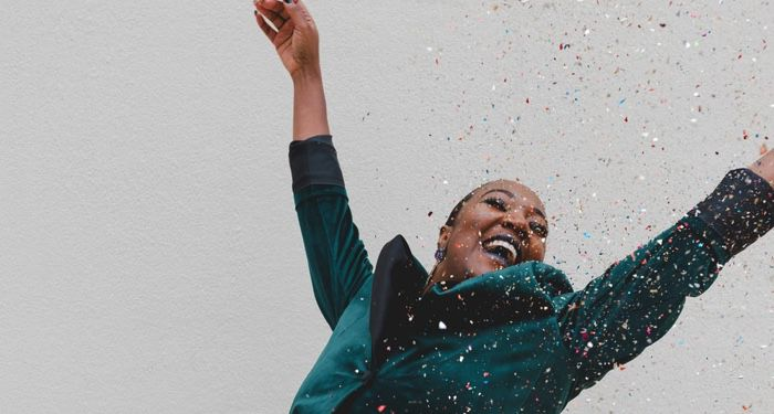 image of Black women in green jacket raising her hands with joy https://unsplash.com/photos/POzx_amnWJw