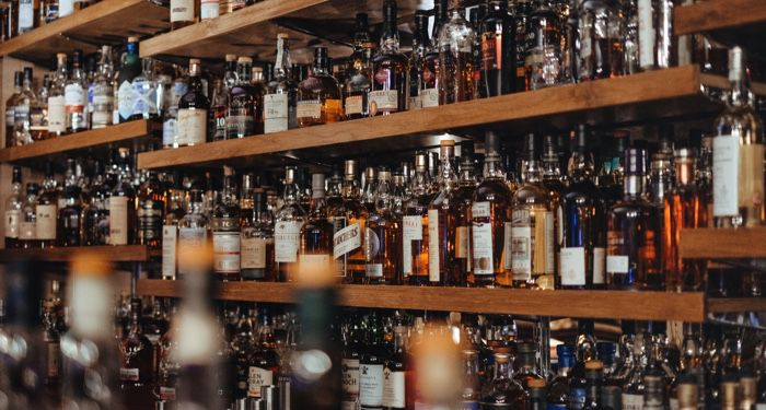 image of bottles of spirits at a hotel bar https://unsplash.com/photos/6UIonphZA5o