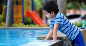 Malaysian South Asian child looking into water fountain