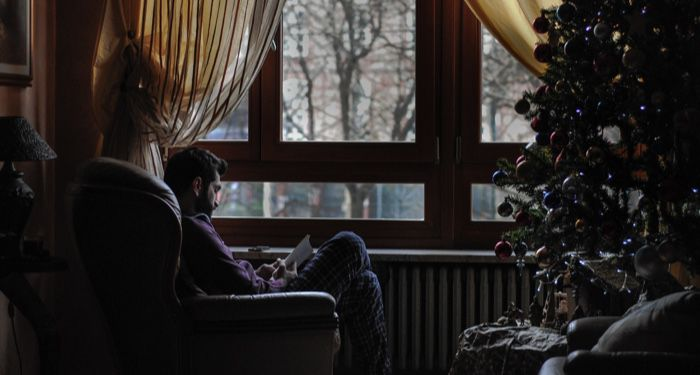 man reading next to the christmas tree in winter