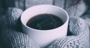 mittened hands holding coffee cup for cozy winter