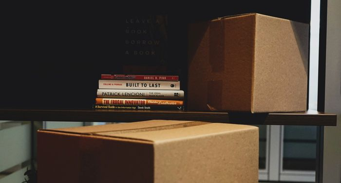 moving boxes near and around a book shelf with a stack of books
