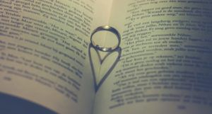 open book with ring inside casting a heart-shaped shadow