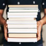 a person holding a stack of books https://www.pexels.com/photo/person-holding-stack-of-books-4218982/