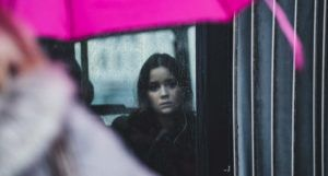 woman looking sadly out of rainy window