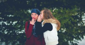 woman whispering a secret into another woman's ear