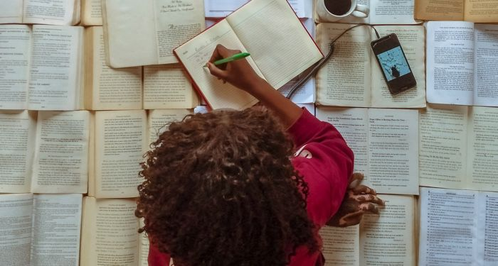 woman writing on top of open books feature 700x375 1.jpg.optimal
