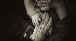 baby hand on top of older persons hand