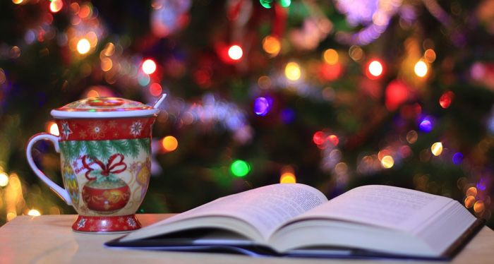 book with holiday mug of cocoa in front of a christmas tree