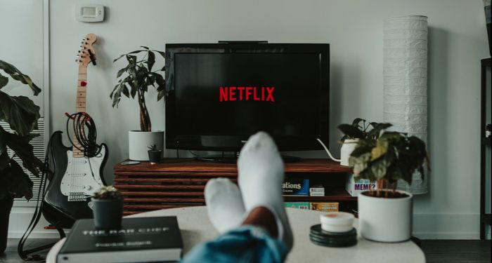 image of a black flat screen TV displaying the Netflix logo and a person's crossed legs https://unsplash.com/photos/yubCnXAA3H8