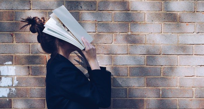 image of woman with book on face against a brick wall.jpg.optimal