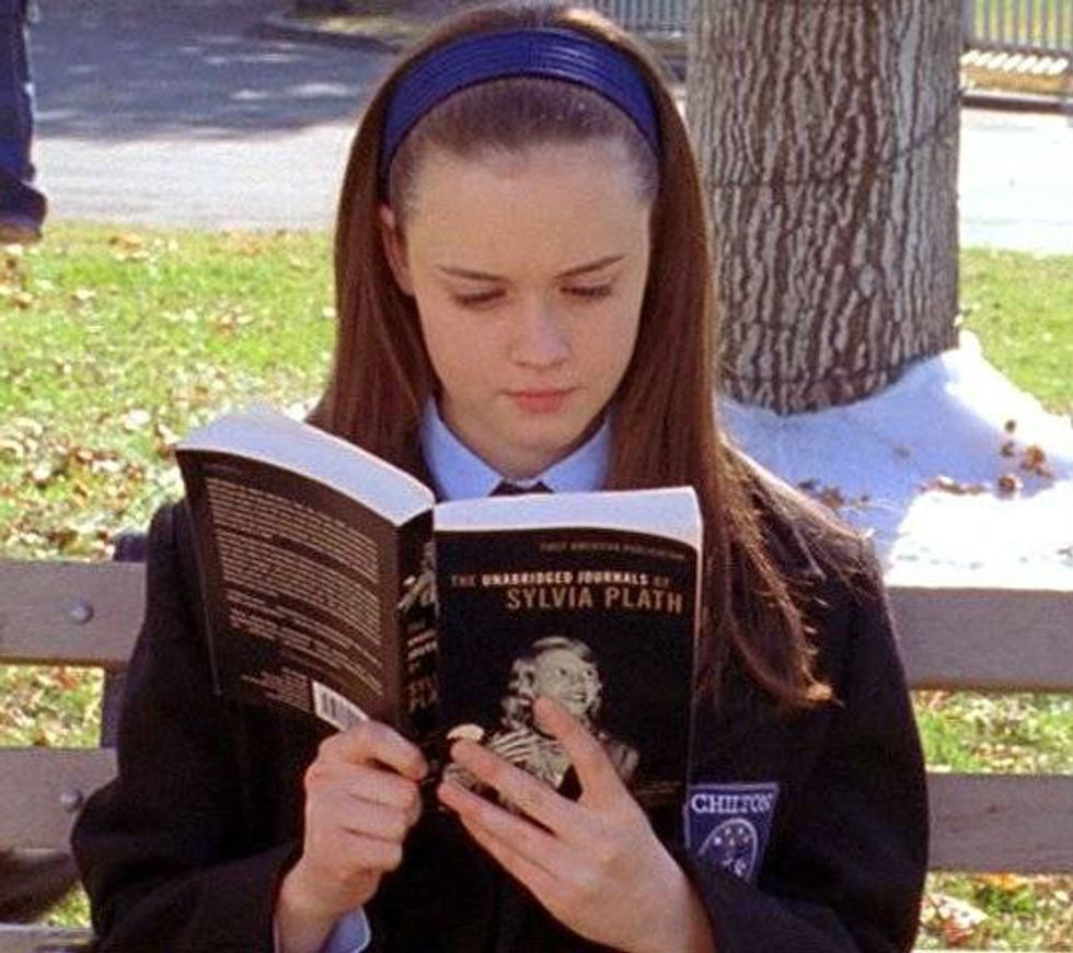 Image from Gilmore Girls of Rory reading the Unabridged Journals of Sylvia Plath