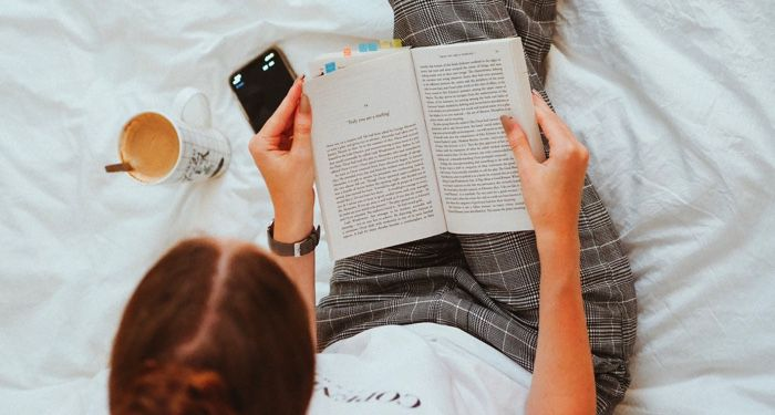 image of a woman reading in bed with cell phone and coffee https://unsplash.com/photos/GrKQjTyMzIE