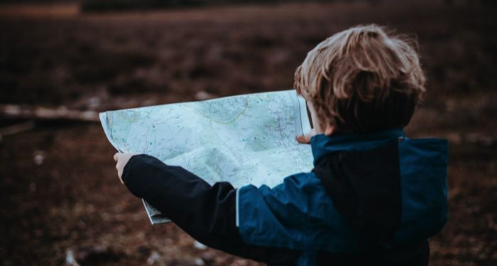 a young child looking at a map outdoors