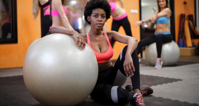 black woman sitting on floor with elbow on exercise ball in gym
