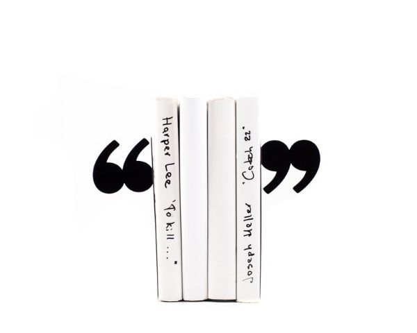 metal bookends that look like quotation marks on either side of a stack of books