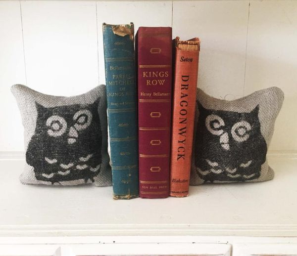 two burlap feedsack pillows with the image of an owl printed on them being used as bookends