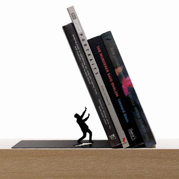 a metal silhouette of a man holding his arms up as it appears books are about to fall on him