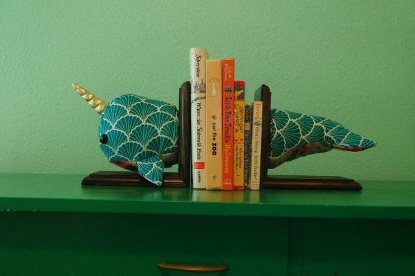 plush narwhal made from geometric fabric, mounted in two pieces on wood bookends