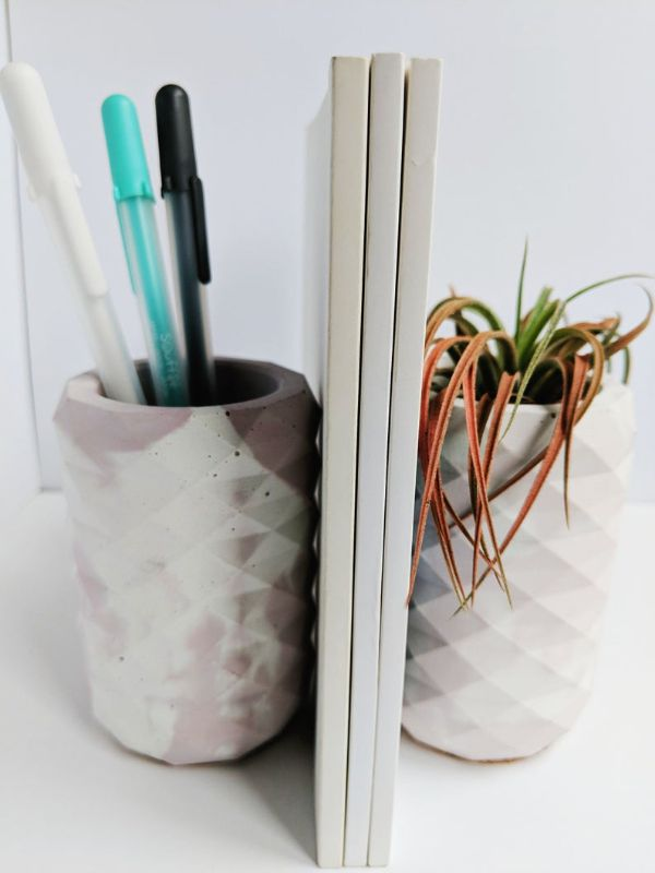 two geometric concrete vases used as bookends, one with pens in it and the other with a plant