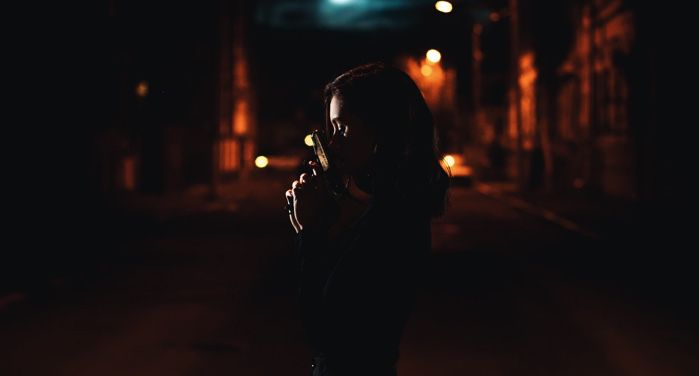 image of woman dressed in black and holding a pistol on a street at night https://unsplash.com/photos/G5nl9_YEXuc