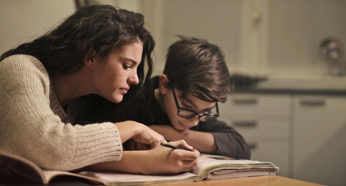 image of a young boy and a woman/parent figure focused on a textbook https://www.pexels.com/photo/focused-students-doing-homework-at-home-3769995/