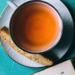 cup of tea with scone on serving plate against teal background with the corner of a book peeking at the bottom