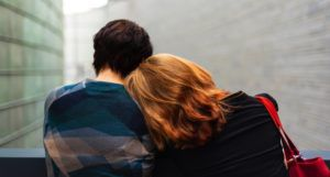 two people leaning on each other with their backs turned toward viewer