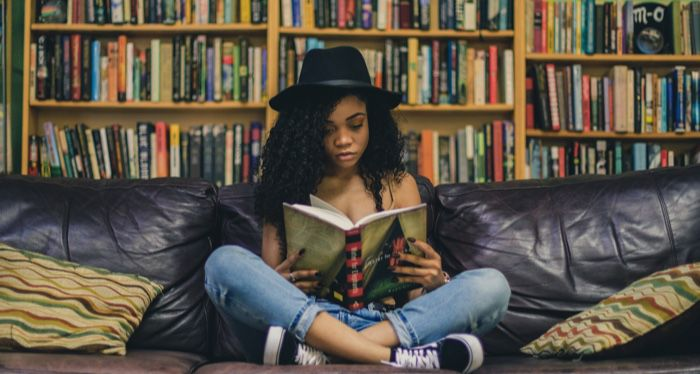 young adult teen woman reading a book in front of bookshelves feature 700x375