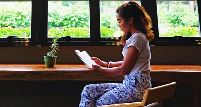 young woman reading a book at a counter in front of windows revealing greenery
