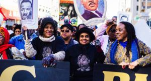 Black women holding Martin Luther King Jr signs at march for civil rights and Black history feature