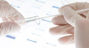 gloved hands swabbing a vial with dna against bright lab backdrop