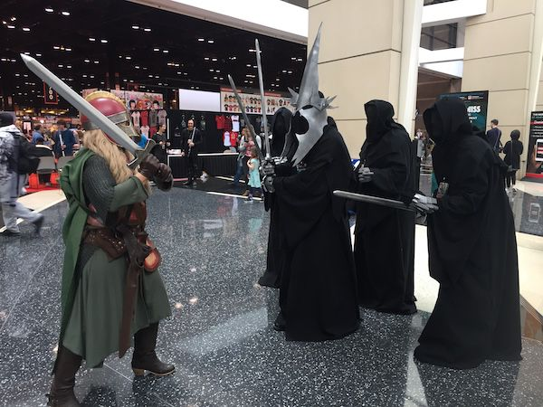 Characters from Lord of the Rings have some fun cosplay. Eowyn in green fights five Nazgul.